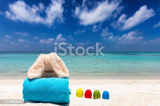 Easter vacation travel concept: relaxed easter bunny with colourful easter eggs on a tropical beach