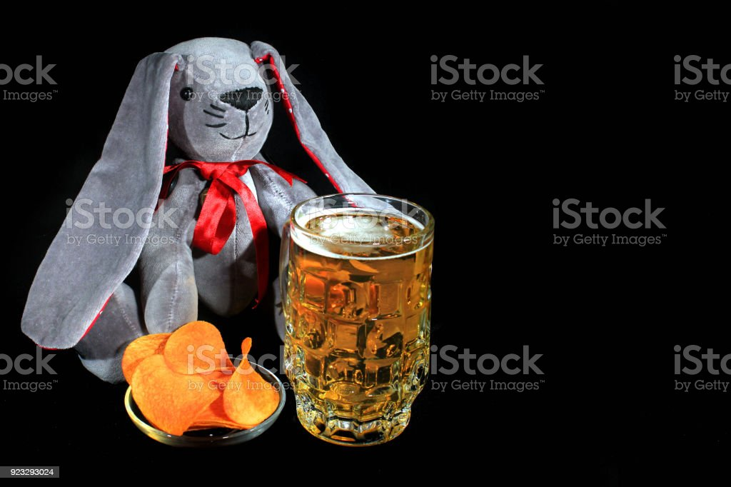 Easter Bunny With Mug Of Beer And Potato Chips Against Black