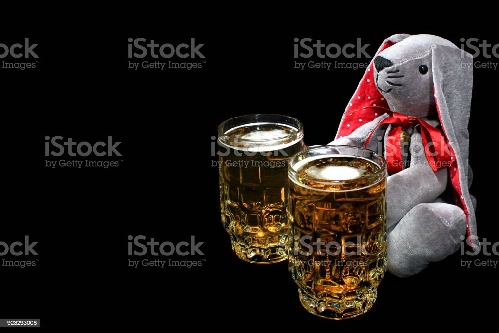 Easter Bunny With Mugs Of Beer Against Black Background Stock Photo