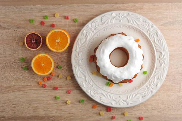 osterkuchen zu ostern mit zuckerguss und orangen - löcherkuchen stock-fotos und bilder