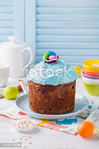 Easter cake with colorful eggs. White and blue wooden background. Copy space