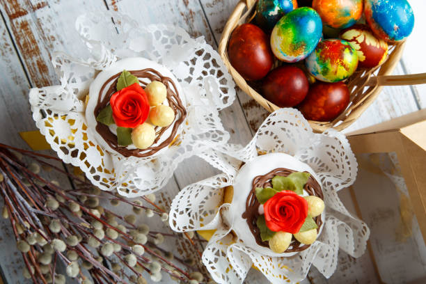 Easter cakes and decorated eggs on white wooden table background. Holiday celebration. Traditional festive meal and dessert. stock photo
