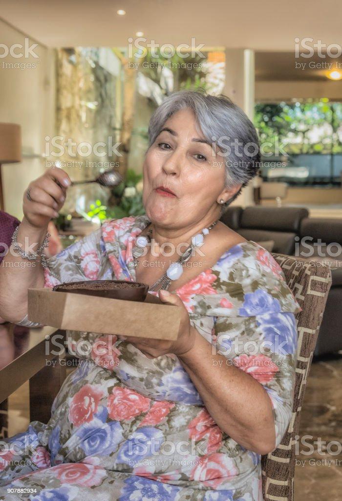 Easter Celebration - Grandmother Tasting Chocolate Eggs stock photo
