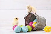 Easter chicken, eggs and decoration in vintage sytle white wooden background
