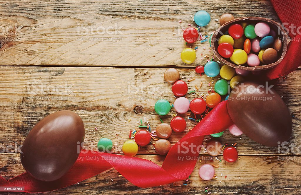 Easter chocolate eggs, candy multicolored, red ribbon stock photo