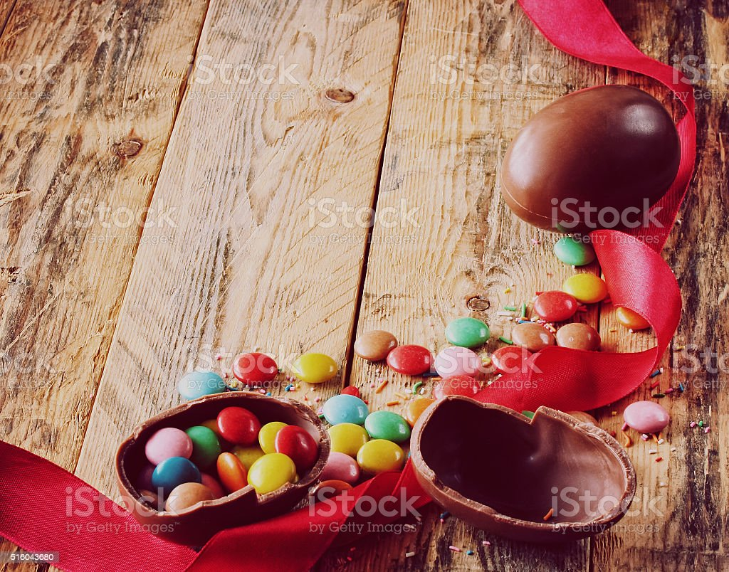 Easter chocolate eggs, candy multicolored, red silk ribbon stock photo