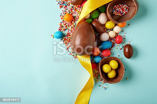 easter chocolate eggs and sugar multicolored sprinkles on blue background with copy space. top view