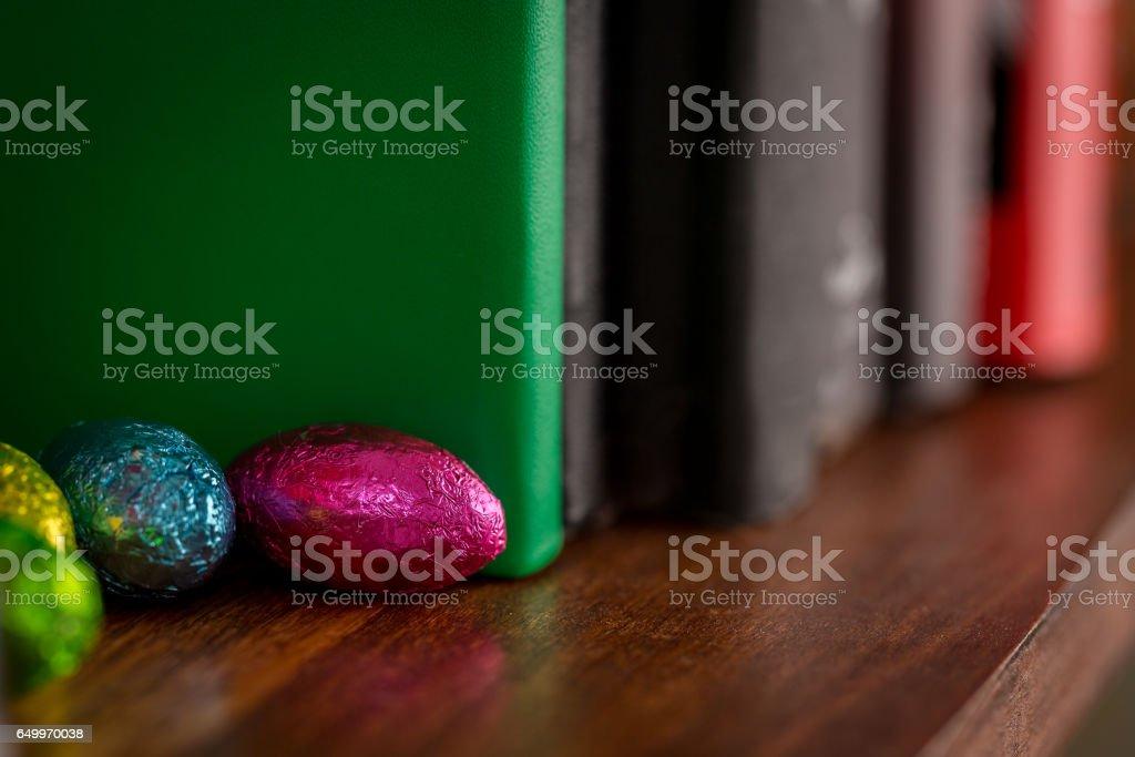 Chocolats de Pâques cachés sur l'étagère de livre photo libre de droits