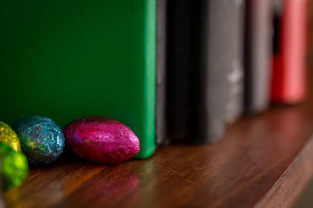 Chocolats de Pâques cachés sur l'étagère de livre - Photo