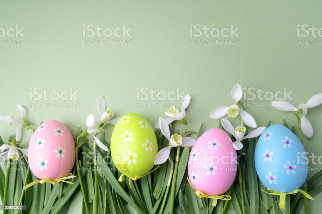 Easter colored eggs in the grass on green background. Top view stock photo