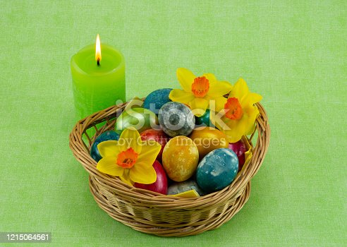 Easter, colored painted eggs in a wicker basket with moss, daffodils and candle on green background