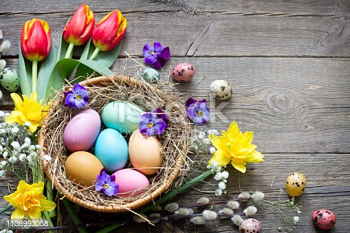912300146 istock photo Easter colorful eggs in the nest with flowers on vintage wooden boards and empty space 1136993058