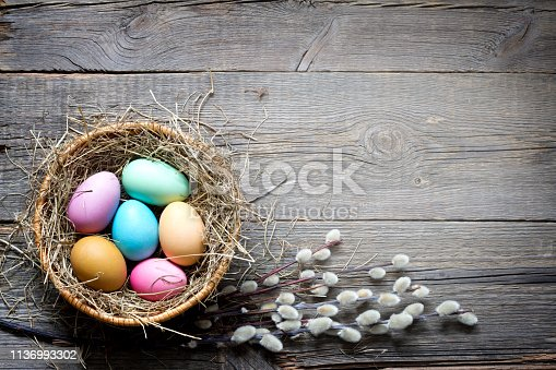 912300146 istock photo Easter colorful eggs in the nest with flowers on vintage wooden boards and empty space 1136993302