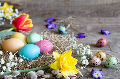912300146 istock photo Easter colorful eggs in the nest with flowers on vintage wooden boards 1136993399