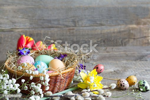 912300146 istock photo Easter colorful eggs in the nest with flowers on vintage wooden boards 1136993559