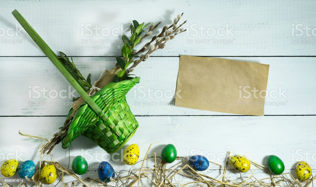 Easter colorful eggs with basket on white wooden background royalty-free stock photo