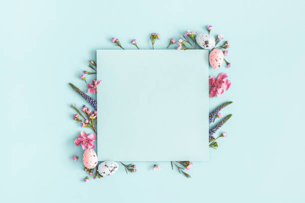 easter composition. easter eggs, flowers, paper blank on pastel blue background. flat lay, top view, copy space - easter foto e immagini stock