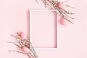 istock Easter composition. Easter eggs, photo frame, white flowers on pastel pink background. Flat lay, top view, copy space 1138994479