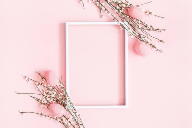 osterkomposition. ostereier, fotorahmen, weiße blüten auf pastellrosa hintergrund. flache, obere ansicht, kopierplatz - schöne osterbilder stock-fotos und bilder