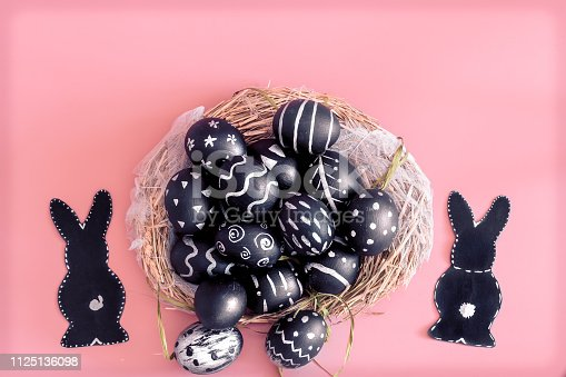 istock Easter composition with eggs and the Easter Bunny on a pink background 1125136098