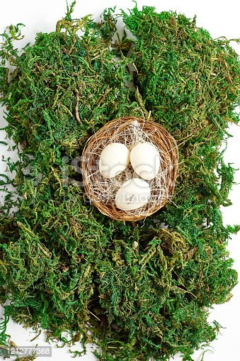 930928526 istock photo easter concept. beautiful festive composition. a small nest with eggs on a green textured background of moss. flat lay, top view 1212777368