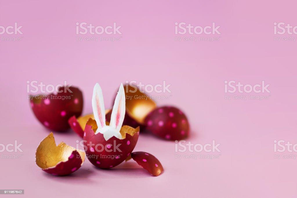 Concepto de semana Santa. Huevos coloreados sobre fondo rosa, conejo de Pascua esconde dentro - foto de stock