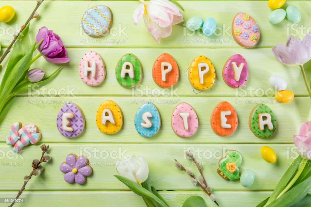 Easter concept - cookies with flowers on green wood background stock photo