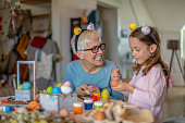 Easter concept. Happy little girl and grandmother prepare chicken eggs for a holiday on a table in the living room