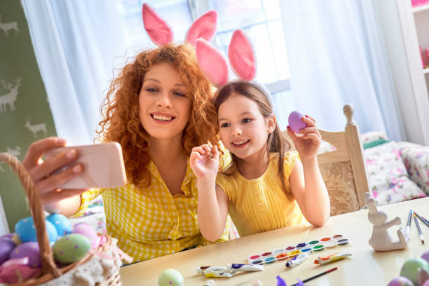 Easter Concept. Mother and daughter in rabbit ears sitting at kitchen coloring eggs taking selfie on smartphone smiling cheerful stock photo