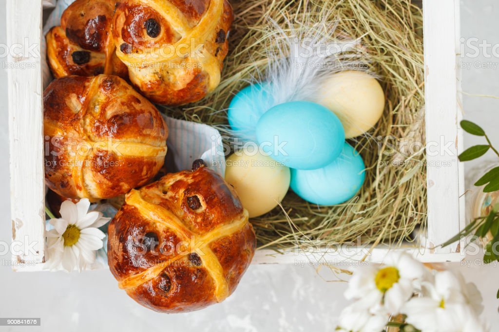 Easter cross buns in a wooden box, painted eggs. Light background, copy space, top view. Easter food concept. stock photo