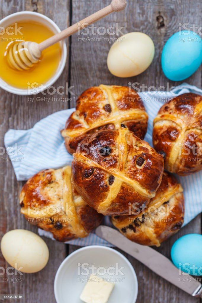 Easter cross buns, painted eggs. Wooden background, copy space, top view. Easter food concept. stock photo