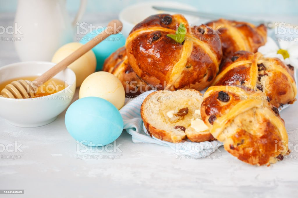 Easter cross buns with honey and butter, painted eggs. Light background, copy space, Easter food concept. stock photo