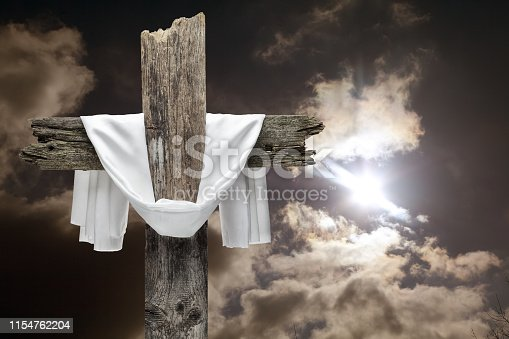 Easter wooden cross on dramatic sky. He is risen concept.