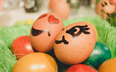istock Easter decoration. Basket with couple of eggs with face expression surrounded by other colorful eggs 1211199240
