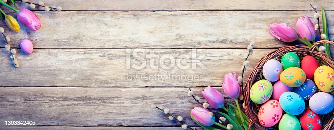 istock Easter Decoration - Painted Eggs In Basket With Tulips On Natural Wooden Plank 1303342405