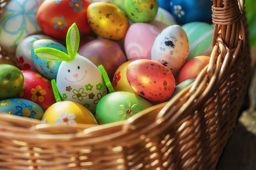 Easter decoration with crafted Easter bunny and eggs in the wicker basket. Spring Easter composition.