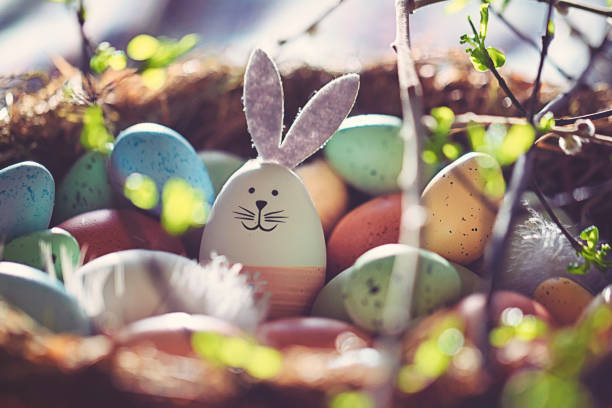 Easter decoration with crafted Easter bunny in the sunny nest stock photo