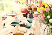 Easter dining table. Decorations, muffins, cake, fruit, beautiful napkins and napkin holders, a centerpiece bouquet of tulips and lovely place settings grace this spring time special occasion dining table.
