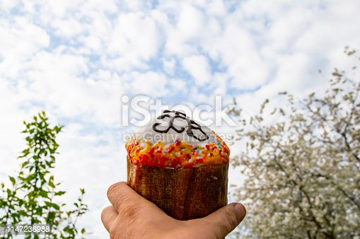 1131445181 istock photo Easter - Easter bread in hand against the sky with clouds. 1147236988