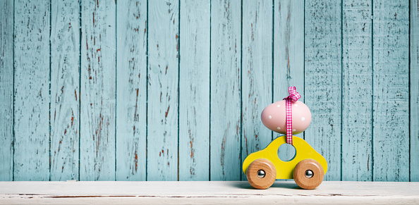 Easter egg and toy car on blue old wood conceptual still life. Panoramic multiple image stich.