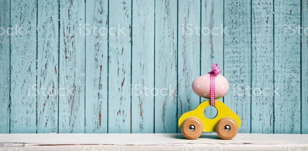 Easter egg and toy car on blue old wood - Travel Holidays Cute Humor Concept stock photo