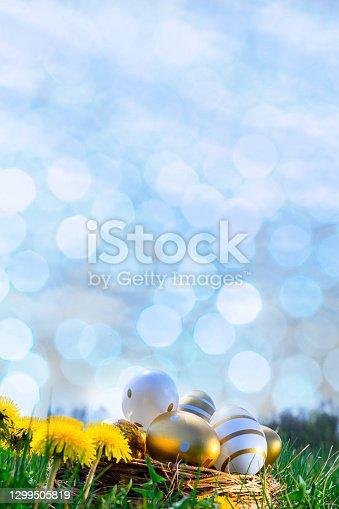 istock Easter egg background. Golden egg with yellow spring flowers in celebration basket on green grass. Easter decoration, foil minimalist egg design, modern design template. 1299505819
