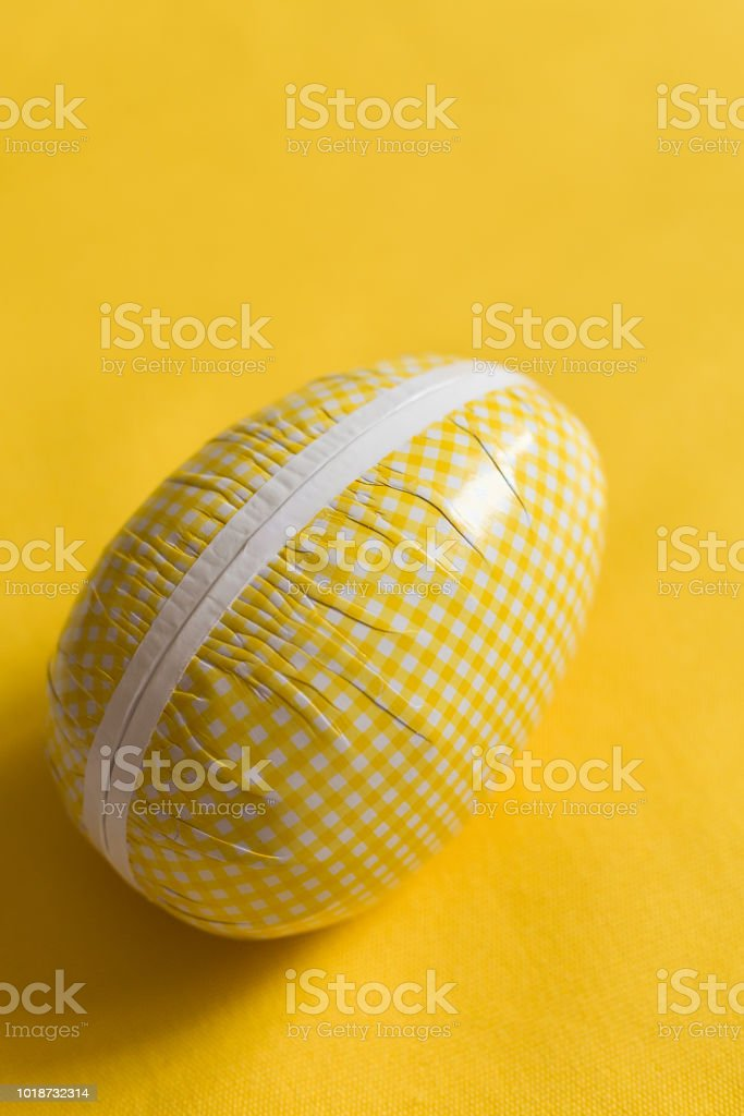 Easter egg box with candy and chocolate, scandinavian tradition. close up on yellow backgorund.  big Easter egg full of sweets and cookies. celebrating Easter. easter surprise. stock photo
