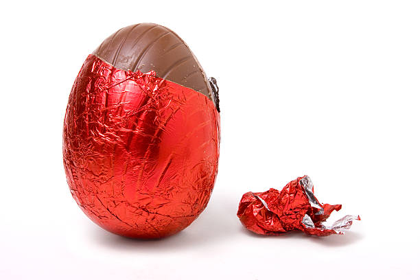 Easter egg covered in red foil on white background stock photo