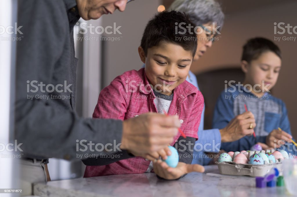 A Grandpa Helps His Grandson Paint An Easter Egg At The Counter Stock Images Page Everypixel