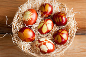 Easter eggs dyed with onion peels, with a pattern of fresh herbs, in a wicker basket. Top view.