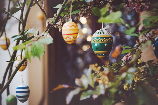 Painted colorful Easter theme eggs hanging on a tree branch with green spring leaves outdoors