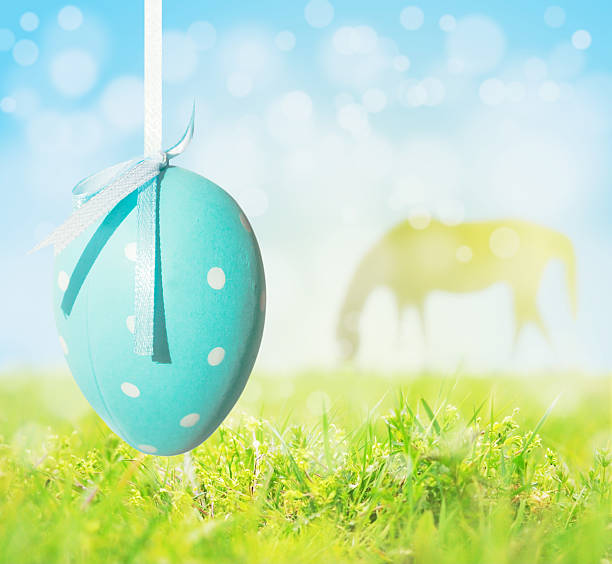 Easter egg hanging on background of grass, sky, grazing horse stock photo
