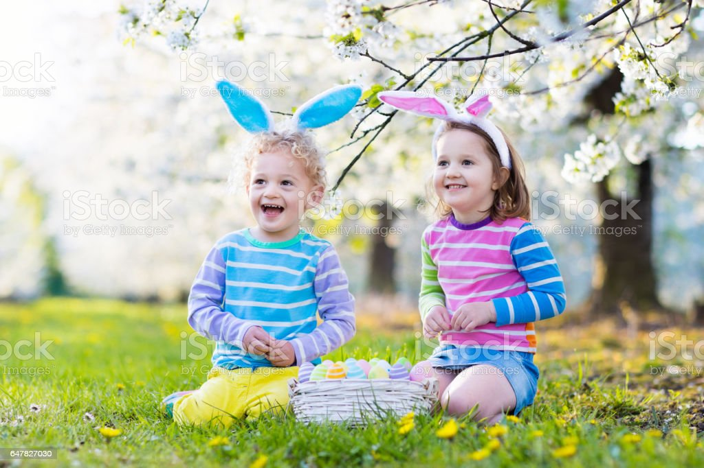 Easter egg hunt. Kids with bunny ears in spring garden. stock photo