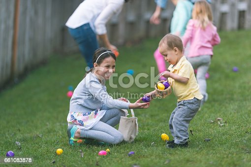 Big sister helps little brother collect Easter eggs